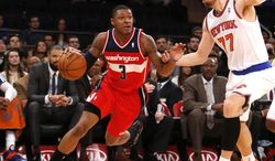 Washington Wizards' Bradley Beal (3) drives against New York Knicks' Andrea Bargnani (77), of Italy, during the second half of an NBA basketball game Monday, Dec. 16, 2013, in New York.  The Wizards won 102-101. (AP Photo/Jason DeCrow)