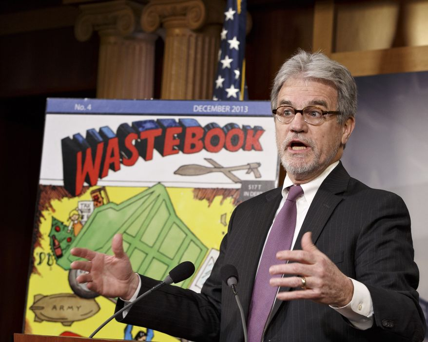 """While the Senate debates the bipartisan budget plan, Sen. Tom Coburn, R-Okla., a longtime deficit hawk, outlines his annual """"Wastebook,"""" which points a critical finger at billions of dollars in questionable government spending, Tuesday, Dec. 17, 2013, during a news conference on Capitol Hill in Washington.  (AP Photo/J. Scott Applewhite)"""