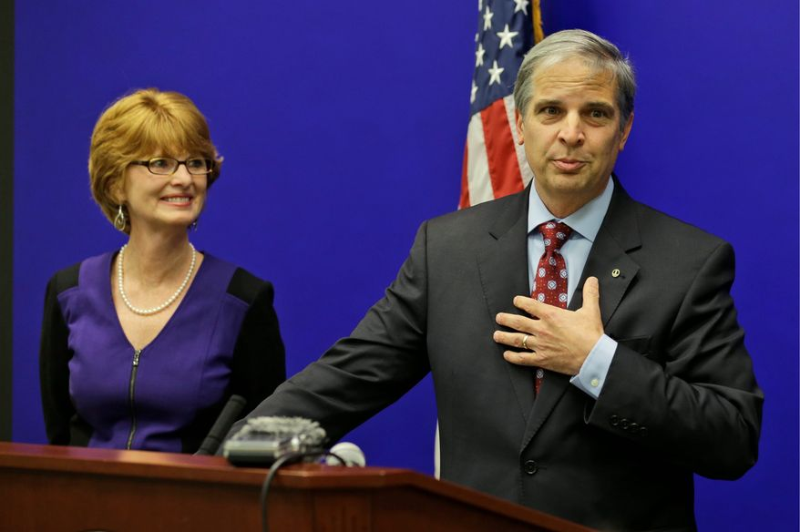ASSOCIATED PRESS PHOTOGRAPHS Virginia State Sen. Mark Obenshain gestures as his wife Suzanne looks on during a news conference at the Capitol in Richmond, Va., Wednesday, Dec. 18, 2013. Obenshain conceded the race for Attorney General to Democrat Mark Herring after a recount showed his losing ground in votes. (AP Photo/Steve Helber)