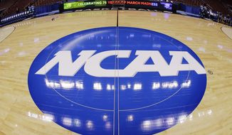 **FILE** In this March 21, 2013, file photo, in this image taken with a fisheye lens, the NCAA logo is displayed at mid-court before Albany's practice for a second-round game of the NCAA college basketball tournament in Philadelphia. (AP Photo/Matt Slocum, File)