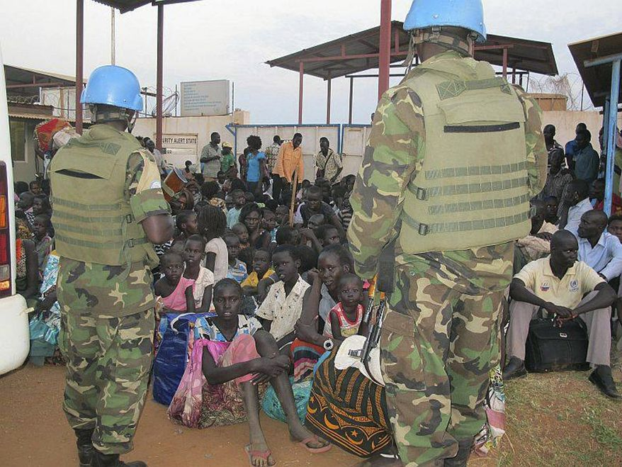 In this image released by the United Nations Mission Juba, United Nations soldiers stand guard as civilians gather at the compound of the United Nations Mission in the Republic of South Sudan (UNMISS), adjacent to Juba International Airport, to take refuge, Wednesday , Dec. 18 , 2013, in Juba, South Sudan. (AP Photo/UNMISS, Rolla Hinedi)