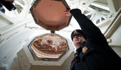 U.S. Capitol Police Officer Adam Taylor holds open one of the coffer windows in the ceiling of the U.S. Capitol dome in Washington on Dec. 19. The dome will soon undergo restoration, budgeted at $60 million, to remove old paint and repair more than 1,000 cracks. (ASSOCIATED PRESS)