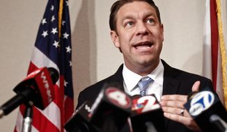 "** FILE ** Congressman Trey Radel addresses the media alongside his wife Amy at his Cape Coral office on Thursday, Dec. 19, 2013. A month after pleading guilty to cocaine-possession charges Radel refused to resign, saying he wants to ""rebuild the trust"" of voters. (AP Photo/Naples Daily News, Scott McIntyre)"