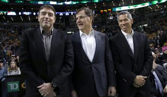 In this photo taken on Dec. 18, 2013, Boston Celtics managing partner Wyc Grousbeck, left, stands with venture capitalist Bob Higgins, center, and team co-owner Mark Wan, right, during a break in the action at an NBA basketball game in Boston. Grousbeck and a group featuring a dozen of his co-owners in the NBA franchise have invested $21 million into Formula E, an all-electric auto racing series that has already attracted interest from environmental celebrities like Leonardo DiCaprio and Richard Branson. The circuit is scheduled to debut in Beijing in September and continue on the streets from Miami to Monaco in a 10-race, Formula One-style championship. (AP Photo/Elise Amendola)