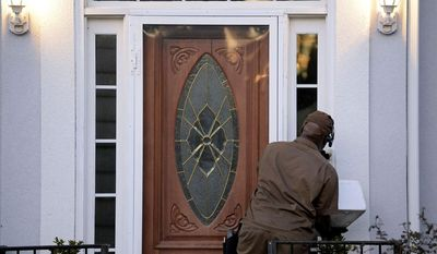 A UPS driver rings the doorbell at the home listed for Ira Curry, one of two Mega Millions lottery ticket winners that were identified by lottery officials in the $636 million drawing, Wednesday, Dec. 18, 2013, in Stone Mountain, Ga. (AP Photo/David Tulis)