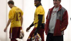 FILE - In this Dec. 11, 2013 file photo, Washington Redskins quarterbacks Kirk Cousins, left, and Robert Griffin III, center, walk behind head coach Mike Shanahan, during their NFL football practice Wednesday, Dec. 11, 2013, in Ashburn, Va.  If these are indeed Mike Shanahan's final days with the Washington Redskins, his legacy will be one of an inability to make things work with his quarterbacks, from Donovan McNabb to Rex Grossman to John Beck to Robert Griffin III.  (AP Photo/Alex Brandon)