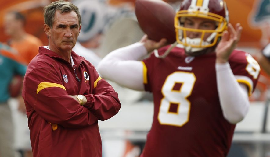 Washington Redskins head coach Mike Shanahan, left, watches quarterback Rex Grossman throw during warm-ups before an NFL football game against the Miami Dolphins, Sunday, Nov. 13, 2011, in Miami. (AP Photo/Hans Deryk)