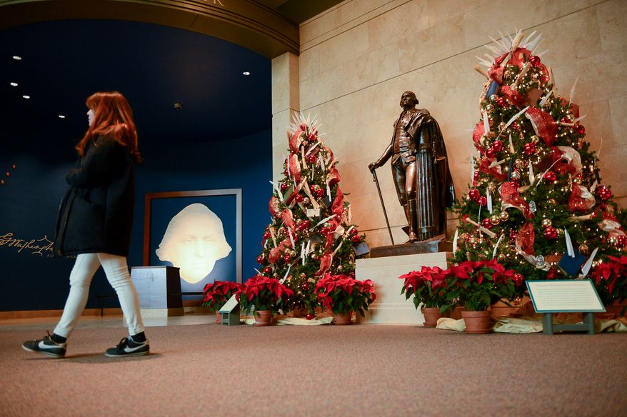 A visitor walks past a statue of George Washington flanked by two Christmas trees during Christmas at George Washington's Mount Vernon, Mount Vernon, Va., Monday, December 16, 2013. Mount Vernon celebrates Christmas with Christmas trees, 18th-century chocolate making, Christmas dancing and story telling, as well as Aladin the Camel. (Andrew Harnik/The Washington Times)