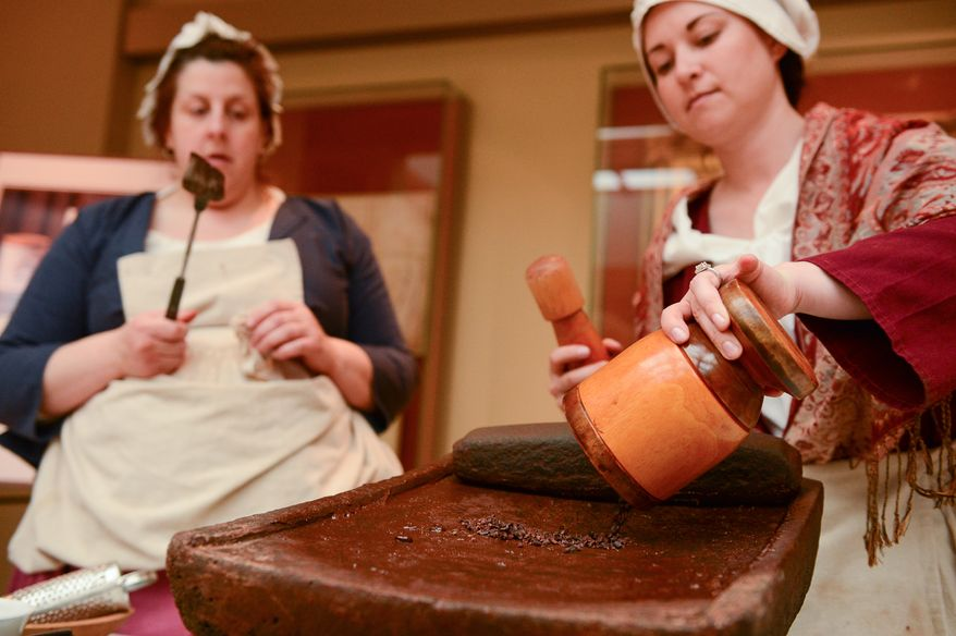Historic Trades Interpreters Melissa Reed, left, and Trish Kristoff prepares to melt chocolate as they work to make drinking chocolate using 18-century techniques as part of Christmas at George Washington's Mount Vernon, Mount Vernon, Va., Monday, December 16, 2013. Mount Vernon celebrates Christmas with Christmas trees, 18th-century chocolate making, Christmas dancing and story telling, as well as Aladin the Camel. (Andrew Harnik/The Washington Times)