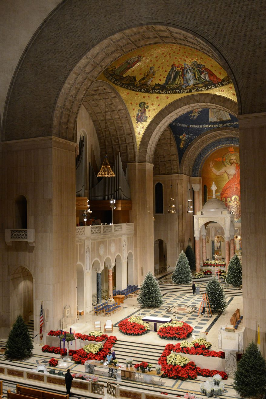 Volunteers help decorate The Basilica of the National Shrine of the Immaculate Conception in Washington, D.C., in preparation for Christmas. (Lloyd Villas/The Washington Times)