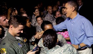 President Obama greets members of the military as he arrives with the first family on Air Force One at Joint Base Pearl Harbor-Hickam, in Honolulu. The first family will be spending its annual winter vacation in Hawaii. (associated press photographs)
