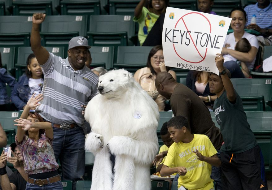 A person dressed as a polar bear and others demonstrate against the Keystone Pipeline as President Barack Obama and the first family attend the Oregon State University versus University of Akron college basketball game at the Diamond Head Classic at the Stan Sheriff Center in Honolulu, Sunday, Dec. 22, 2013. Michelle Obama's bother, Craig Robinson, is the coach for Oregon State. The first family is in Hawaii for their annual holiday vacation. (AP Photo/Carolyn Kaster)