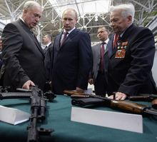 """Russian President Vladimir Putin (center) met with Gen. Mikhail Kalashnikov (right) at a manufacturing plant in 2010 and once hailed his famous assault rifle as """"a symbol of the creative genius of our people."""" (RIA-Novosti via Associated Press)"""