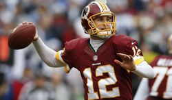 Washington Redskins quarterback Kirk Cousins passes the ball during the first half of an NFL football game against the Dallas Cowboys in Landover, Md., Sunday, Dec. 22, 2013. (AP Photo/Evan Vucci)