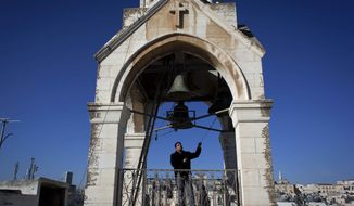 In this photo made Sunday, Dec. 22, 2013, Khadir Jaraiseh, 22, pulls the ropes of four bells in a short tower on the roof of the Church of the Nativity, for prayer services of the Armenian Apostolic Church, in the West Bank city of Bethlehem. (AP Photo/Nasser Nasser) ** FILE **