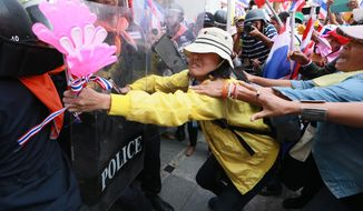 Thai anti-government protesters, right, push through line of riot police during a rally at the Department of Special Investigation (DSI) on the outskirts of Bangkok, Thailand Monday, Dec. 23, 2013. About 5,000 protesters took part in the rally and later stormed into the DSI office building when the DSI has charged the protest leaders on illegal demonstrations and frozen their bank accounts last week. (AP Photo/Wason Wanichakorn)