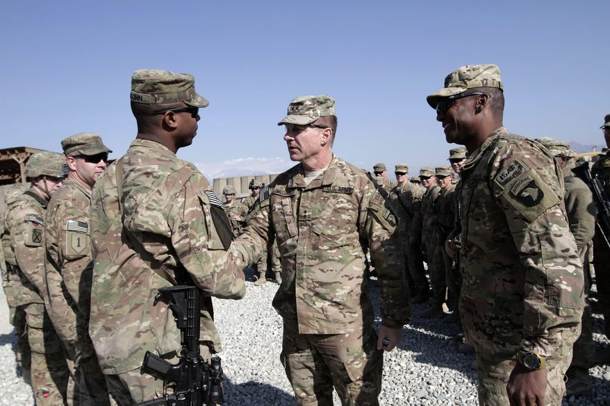 U.S. Maj. Gen. James C. McConville, center, visits troops in Jalalabad, base east of Kabul, Afghanistan, Tuesday, Dec. 24, 2013. The commander of NATO forces in eastern Afghanistan spent Christmas Eve visiting U.S. troops at bases across the mountainous region to bring them holiday greetings and gifts for a few lucky soldiers. (AP Photo/Rahmat Gul)