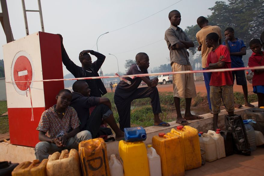 People waiting to purchase fuel hold their places in line with jerrycans, at a gas station that was closed, awaiting the arrival of military police, in Bangui, Central African Republic, Tuesday, Dec. 24, 2013. With few gas stations open and reliable fuel hard to find, people lined up as early as 4 a.m. at this station, which wasn't slated to open until police protection arrived around 9 or 10 a.m. (AP Photo/Rebecca Blackwell)