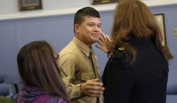 Lance Cpl. Christopher Mohedano-Hernandez, center, is hugged by family members after participating in an adoption ceremony in Mineola, N.Y., Tuesday, Dec. 24, 2013. The U.S. Marine home on leave has been formally adopted by his stepfather in a Christmas Eve adoption ceremony held in a suburban New York courtroom. Mohedano-Hernandez is the latest in what experts call a growing trend of adult adoptions. (AP Photo/Seth Wenig)