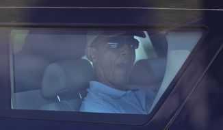 President Barack Obama is seen through the tinted window of his motorcade vehicle as he is driven through the Kailua, Hawaii, neighborhood where he is spending his annual holiday vacation with his family, Tuesday, Dec. 24, 2013, en route to Marine Corps Base Hawaii in Kaneohe, Hawaii, to play golf. The first family is in Hawaii for their annual holiday vacation. (AP Photo/Carolyn Kaster)