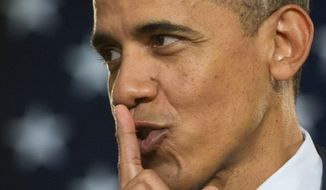 President Obama signals quiet during a speaking appearance.