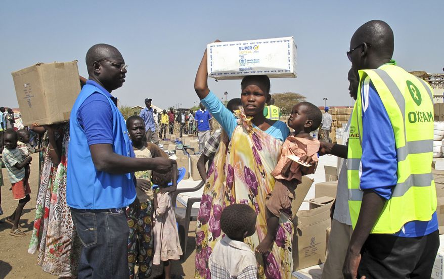 In this photo released by the World Food Programme (WFP), a displaced woman and child receive food assistance from workers of WFP and non-governmental organizations such as Oxfam, right, at the U.N. compound where she has taken shelter in Juba, South Sudan Tuesday, Dec. 24th, 2013. South Sudan's military spokesman says there is increasing tension at a United Nations camp in the rebel-held city of Bor because armed elements have entered the congested area where the U.N. says about 17,000 civilians are seeking protection. (AP Photo/WFP, George Fominyen)