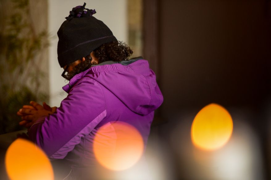 Lauren Hutchinson, 10, of Hyattsville, Md., stops to pray in front of a manger scene after helping to light nearly 1,000 luminarias set up along the exterior of the historic Franciscan Monastery of the Holy Land, Washington, D.C., Tuesday, December 24, 2013. The luminaries, which will remain lit through New Year's Eve, are each dedicated to an individual for whom prayers will be offered throughout Christmas week.