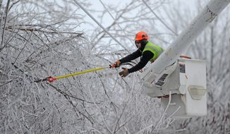 Andrew Powers, an arborist with Asplundh Tree Experts, clears power lines from iced branches along Mayflower Heights Drive in Waterville, Maine, on Monday, Dec. 23, 2013. (AP Photo/The Central Maine Morning Sentinel, Michael G. Seamans)