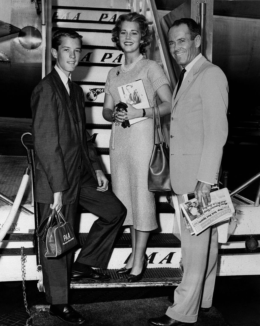 FILE - In this June 25, 1957 file photo, movie actor Henry Fonda, right, with his children, Jane and Peter, are shown at New York International Airport boarding a clipper airplane for Europe where they'll spend the summer seeing sights.   On on Saturday, April 27, 2013, Jane Fonda, the 75-year-old Oscar winner , will place her hand and footprints next to her father's in the concrete shrine to celebrity outside Hollywood's TCL Chinese Theatre. Then she'll present a special screening of the film she made with her dad, On Golden Pond. The cement and cinematic tribute is part of the 2013 TCM Classic Film Festival, which is honoring Jane Fonda.(AP Photo, File)