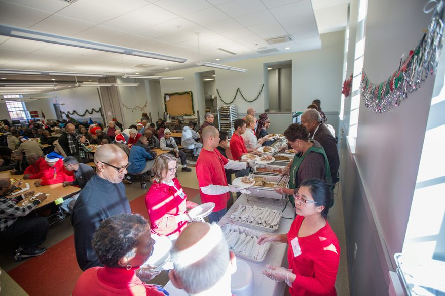 Volunteers from several church organizations line up Wednesday to make holiday meals for homeless guests at the Central Union Mission in the District. (photographs by andrew s. geraci/the washington times)