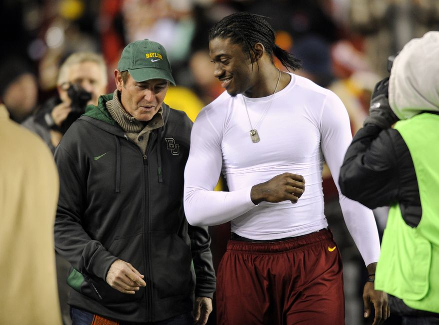 Washington Redskins quarterback Robert Griffin III, second from left, walks with Baylor head football coach Art Briles, left, before an NFL football game against the Dallas Cowboys, Sunday, Dec. 30, 2012, in Landover, Md. (AP Photo/Nick Wass)