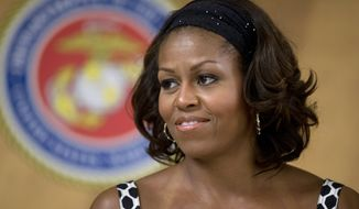 First lady Michelle Obama looks out from the stage as President Barack Obama speaks to members of the military and their families in Anderson Hall at Marine Corps Base Hawaii, Wednesday, Dec. 25, 2013, in Kaneohe Bay, Hawaii. The first family is in Hawaii for their annual holiday vacation. (AP Photo/Carolyn Kaster)