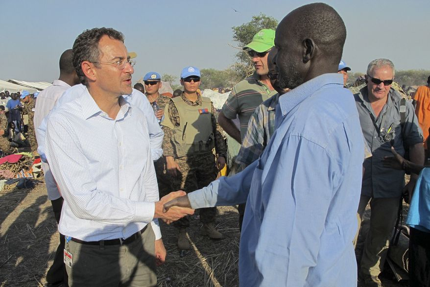 In this photo taken Tuesday, Dec. 24, 2013, and released by the United Nations Mission in South Sudan (UNMISS) on Wednesday, Dec. 25, 2013, the U.N.'s top humanitarian official in the country Toby Lanzer, left, makes a visit to assess the humanitarian situation at the U.N. compound where many displaced have sought shelter in Bentiu, in oil-rich Unity state, in South Sudan. (AP Photo/UNMISS, Anna Adhikari)