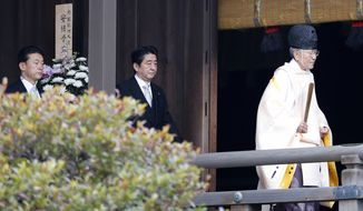 """Japanese Prime Minister Shinzo Abe, center, follows a Shinto priest to pay respect for the war dead at Yasukuni Shrine in Tokyo Thursday, Dec. 26, 2013. Abe visited Yasukuni war shrine in a move sure to infuriate China and South Korea. The visit to the shrine, which honors 2.5 million war dead including convicted class A war criminals, appears to be a departure from Abe's """"pragmatic"""" approach to foreign policy, in which he tried to avoid alienating neighboring countries. It was the first visit by a sitting prime minister since Junichiro Koizumi went to mark the end of World War II in 2006. (AP Photo/Shizuo Kambayashi)"""
