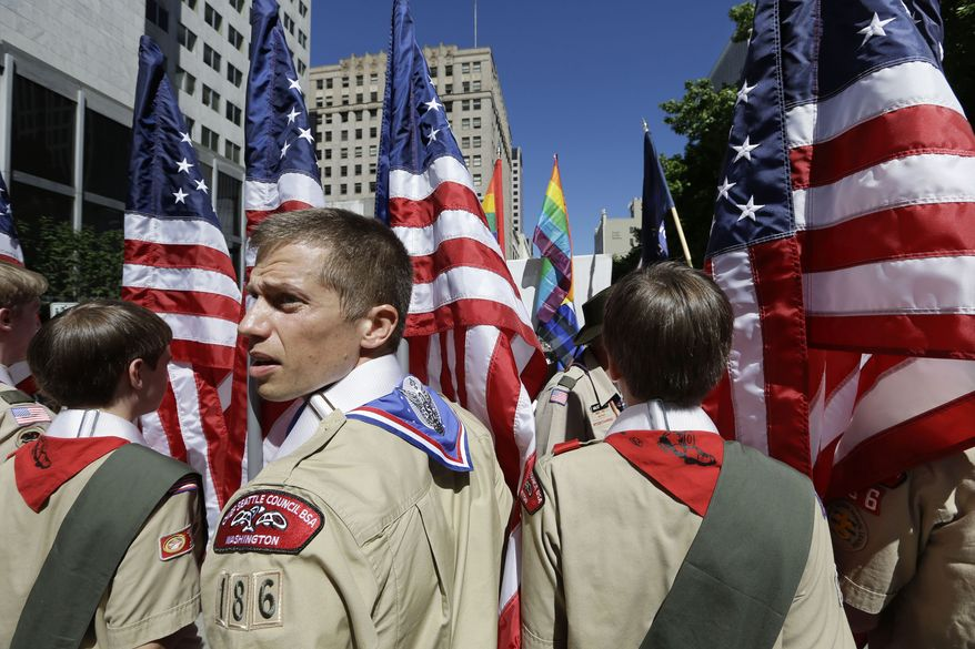 ** FILE ** In this June 30, 2013, file photo, Boy Scouts from the Chief Seattle Council carry U.S. flags as they prepare to march in the Gay Pride Parade in downtown Seattle. The Boy Scouts of America, in the most contentious change of membership policy in a 103-year history, will accept openly gay youths in Scout units starting on New Year's Day 2014. (AP Photo/Elaine Thompson, File)