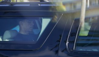 President Barack Obama is seen through the window of his motorcade vehicle as he is driven on Marine Corps Base Hawaii, in Kaneohe Bay, Hawaii, after the morning workout, Friday, Dec. 27, 2013. (AP Photo/Carolyn Kaster)