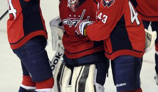 Washington Capitals defenseman John Carlson, left, and Tom Wilson (43) celebrate 3-2 win over the New York Rangers with goalie Philipp Grubauer, center, in an NHL hockey game, Friday, Dec. 27, 2013, in Washington. (AP Photo/Nick Wass)