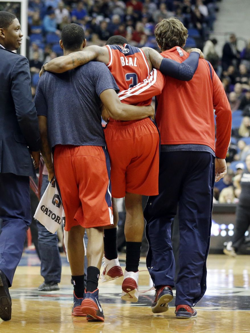 Washington Wizards' Bradley Beal is helped off the court after an injury during the second half of an NBA basketball game against the Minnesota Timberwolves, Friday, Dec. 27, 2013, in Minneapolis. The Timberwolves won 120-98. (AP Photo/Jim Mone)