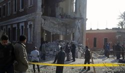 **FILE** Security personnel and others inspect the site of an explosion outside a military intelligence building in Anshas, a rural village in Sharqiya province, nearly 50 kilometers (30 miles) northeast of Cairo, on Dec. 29, 2013. Attacks on security targets have become frequent following the July 3 ouster of Islamist President Mohammed Morsi. (Associated Press)
