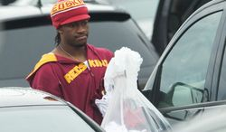 After cleaning out his locker at Redskins Park on Monday, quarterback Robert Griffin III heads to his car after a 3-13 season. He thanked Mike Shanahan for drafting him. (Associated Press)