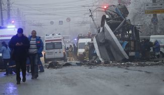 Ambulances line up a site of a trolleybus explosion, background, in Volgograd, Russia Monday, Dec. 30, 2013.  A bomb blast tore through the trolleybus in the city Volgograd on Monday morning, killing at least 10 people a day after a suicide bombing that killed at 17 at the city's main railway station. (AP Photo/Denis Tyrin)