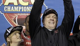 FILE - In this file photo from Dec. 7, 2013, Florida State head coach Jimbo Fisher, right, holds up a trophy as his son, Trey, left, looks on after the Atlantic Coast Conference Championship NCAA football game in Charlotte, N.C., Florida State defeated Duke 45-7. The No. 1-ranked Florida State held their final workout on campus Monday, Dec. 30 2013, before flying to California to face No. 2 Auburn in the BCS NCAA college football championship game. (AP Photo/Bob Leverone, file)