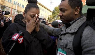 Nailah Winkfield, left, mother of 13-year-old Jahi McMath, is comforted by brother Omari Sealey as she talks to the media outside Children's Hospital Oakland, Monday, Dec. 30, 2013 in Oakland, Calif. McMath, who was declared brain dead after complications of a tonsillectomy, will now stay on a ventilator through Jan. 7. (AP Photo/The Tribune, D. Ross Cameron)
