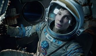 "Sandra Bullock stars in ""Gravity,"" a riveting movie about a medical engineer and an astronaut trying to survive after an accident leaves them adrift in space. (ASSOCIATED PRESS)"