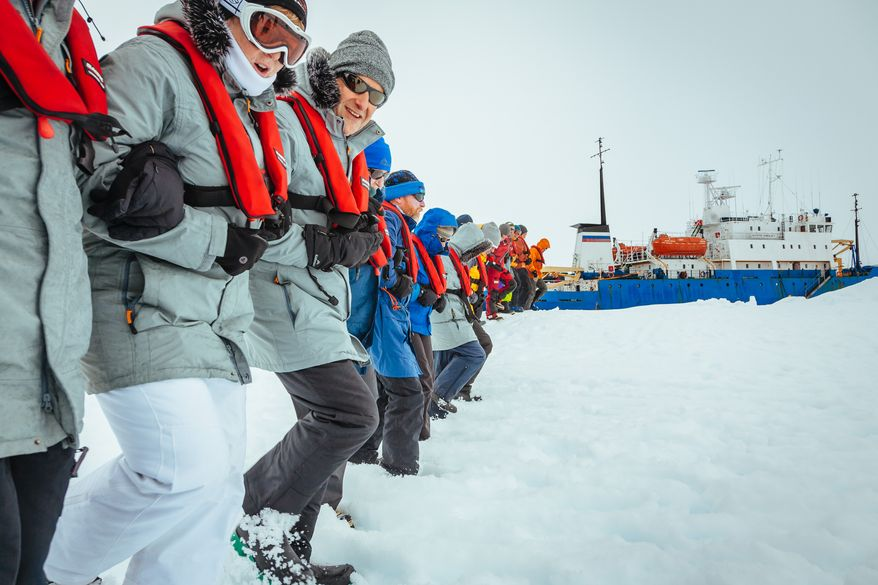 In this Tuesday, Dec. 31, 2013, image provided by Australasian Antarctic Expedition/Footloose Fotography, passengers from the Russian ship MV Akademik Shokalskiy link arms and stamp out a helicopter landing site on the ice near the trapped ship 1,500 nautical miles south of Hobart, Australia. (AP Photo/Australasian Antarctic Expedition/Footloose Fotography, Andrew Peacock)