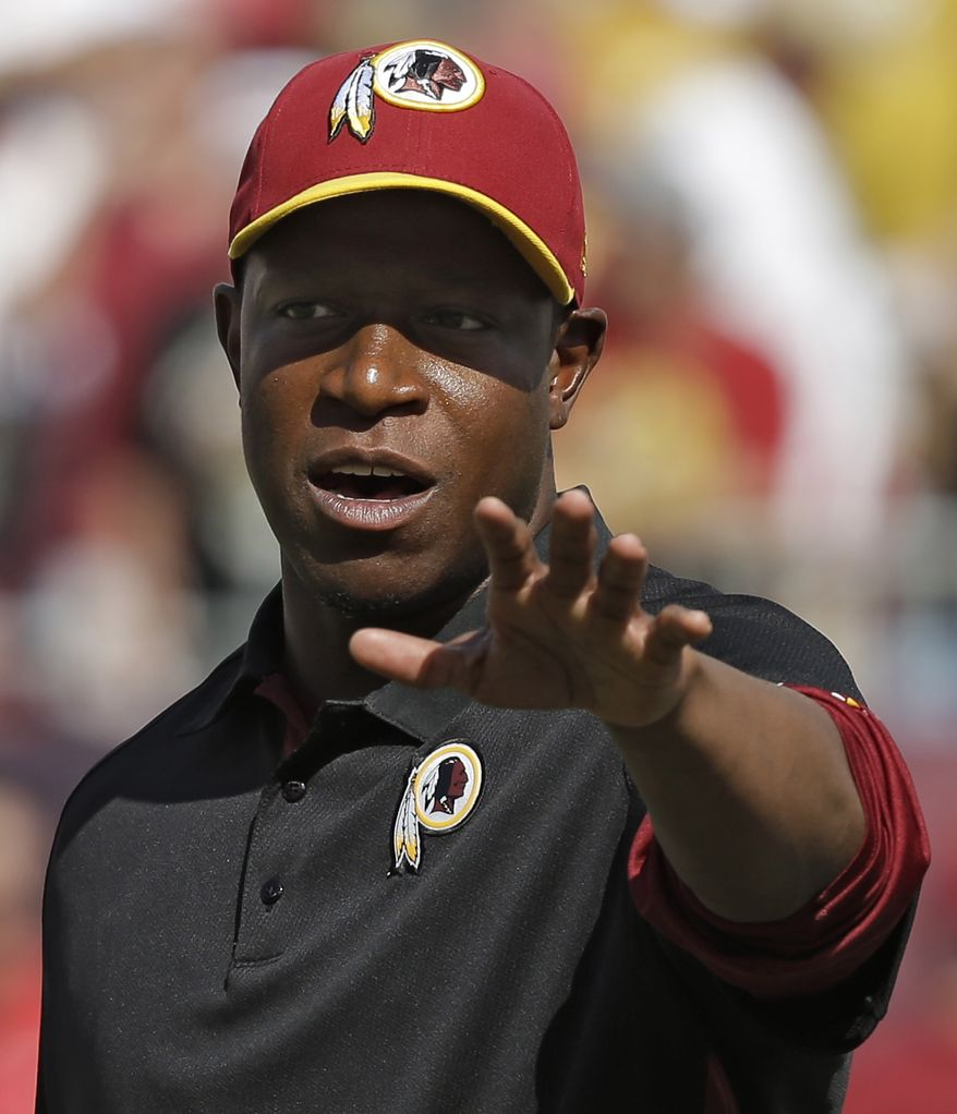 Washington Redskins defensive back coach Raheem Morris waves to fans along the sideline before the start of an NFL football game against the Tampa Bay Buccaneers Sunday, Sept. 30, 2012, in Tampa, Fla. Morris was the Buccaneers' head coach last season. (AP Photo/Chris O'Meara)