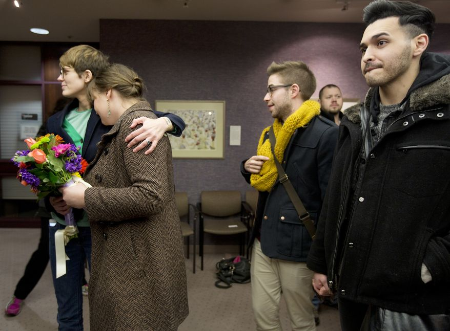 FILE - In this Dec. 20, 2013, file photo, same-sex couples Natalie Dicou, left, and Nichole Christensen, middle left, and James Goodman, middle right, and Jeffrey Gomez, right, wait in line to get a marriage license at the Salt Lake County Clerk's Office in Salt Lake City. Utah asked the U.S. Supreme Court on Tuesday, Dec. 31, 2013, for an emergency stay on more than 900 marriage licenses issued to gay couples since Dec. 20. (AP Photo/Kim Raff, File)