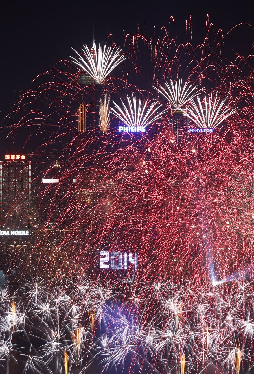 Fireworks explode at the Hong Kong Convention and Exhibition Centre over the Victoria Harbor during New Year's celebrations in Hong Kong, Wednesday, Jan. 1, 2014. (AP Photo/Kin Cheung)