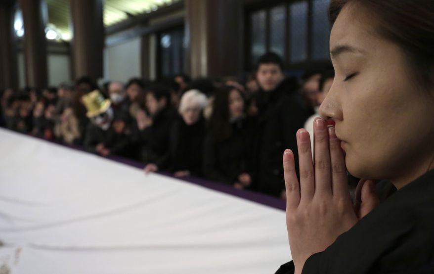 A woman prays at the start of the New Year at Zojoji Buddhist temple in Tokyo, early Wednesday, Jan. 1, 2014. (AP Photo/Shizuo Kambayashi)