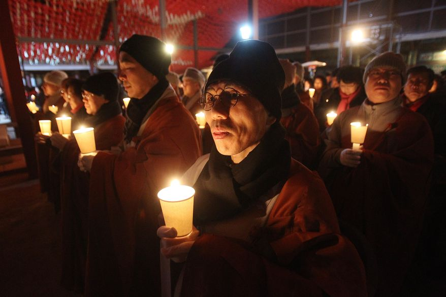 Buddhist monks hold candle lights during New Year's Eve celebrations at Bongeun Buddhist temple in Seoul, South Korea, Wednesday, Jan. 1, 2014. (AP Photo/Ahn Young-joon)